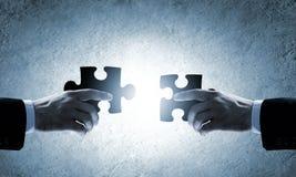 zwei Hände mit verschiedenen Stücken des Puzzlespiels Lizenzfreie Stockfotografie