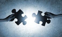 zwei Hände mit verschiedenen Stücken des Puzzlespiels Lizenzfreies Stockfoto