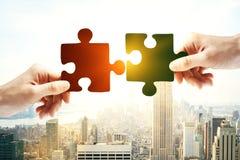 zwei Hände mit verschiedenen Stücken des Puzzlespiels lizenzfreie stockfotos
