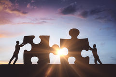 zwei Hände mit verschiedenen Stücken des Puzzlespiels lizenzfreies stockbild