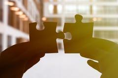 Zwei Hände schließen ein Puzzlespiel an Stockfotos