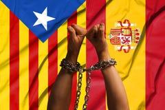 Zwei Hände shackled eine Metallkette auf dem Hintergrund von Flaggen von Katalonien und von Spanien Lizenzfreie Stockfotos