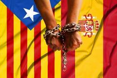 Zwei Hände shackled eine Metallkette auf dem Hintergrund von Flaggen von Katalonien und von Spanien stockfotografie