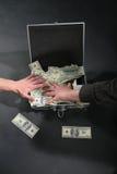 Zwei Hände und Koffer mit Dollar lizenzfreie stockfotos