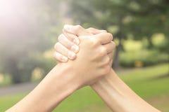 Zwei Hände von Jugendlichen kämpfen unter selbst im Park und im Wald stockfotografie