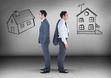 Zwei Häuser mit dem Geschäftsmann, der in den entgegengesetzten Richtungen schaut Stockfotos