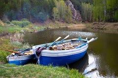 Zwei hölzerne Boote mit Rudern auf der Bank des Waldflusses, Wald stockbild