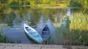 Zwei hölzerne Flussboote im Fluss umgeben mit grüner Vegetation Lizenzfreies Stockfoto