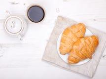 Zwei Hörnchen mit Kaffee auf der weißen Tabelle Lizenzfreies Stockbild