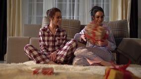 Zwei hübsche erwachsene Schwesterzwillinge, die Weihnachts- oder des neuen Jahresgeschenke mit einander auf gemütlichem Wohnzimme stock footage