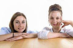 Zwei hübsche Frauen, die entlang der Kamera anstarren Stockfotografie