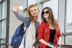 Zwei hübsche Frauen, die im Anschluss mit einem Koffer, einem Rucksack und einem Pass, Blick im Telefon stehen Lizenzfreies Stockfoto