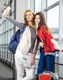 Zwei hübsche Frauen, die im Anschluss mit einem Koffer, einem Rucksack und einem Pass, Blick im Telefon stehen Stockbilder