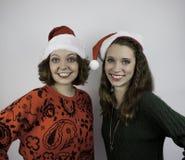 Zwei hübsche Frauen, die Sankt-Hüte tragen stockfotos