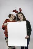 Zwei hübsche Frauen, die Zeichen für Kopienraum halten Stockbilder