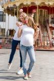 Zwei hübsche Frauen im Vergnügungspark, der Spaß hat und Bonbons, glückliche Familie isst Gleichgeschlechtliche lesbische Familie Stockfotos