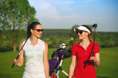 Zwei hübsche Frauengolfspieler, die am Golfplatz gehen stockfoto