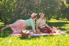 Zwei hübsche Freundinnen, die auf der roten Decke auf dem grünen Gras und Sommerpicknick haben sitzen glückliche Frau, die Rest u stockfotografie
