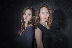 Zwei hübsche Freundinnen, die zusammen zurück zu Rückseite stehen Betrachten der Kamera Atelieraufnahme in der noir Art Stockfoto