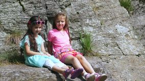 Zwei hübsche Mädchen, Kinder, sitzen auf einer Leiste im Felsen , wirbelt ein schöner orange Gebirgsschmetterling und fliegt über stock video