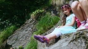 Zwei hübsche Mädchen, Kinder, sitzen auf einer Leiste im Felsen , wirbelt ein schöner orange Gebirgsschmetterling und fliegt über stock video footage