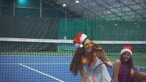 Zwei hübsche Mädchen sitzen auf dem Tennisplatz in den Zusätzen des neuen Jahres stock video footage