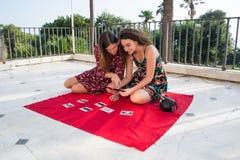 Zwei hübsche Mädchen wählen Fotos für Social Media lizenzfreie stockfotos