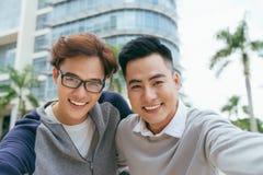 Zwei h?bsch und junge asiatische M?nner, die selfie Portr?t auf Smartphone im Flughafen - Bild machen stockfotografie