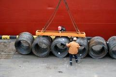 Zwei Hafenarbeiter reparieren eine Ladung eines Drahts für Laden Stockbilder