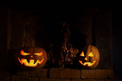 Zwei Halloween-Kürbise am Kamin mit Feuer in der Dunkelheit mit y Stockfotografie