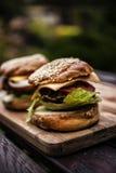 Zwei Hamburger auf einem Brett lizenzfreies stockbild