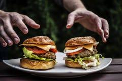 Zwei Hamburger mit den Händen stockfoto