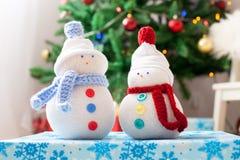 Zwei handgemachte Schneemänner mit Weihnachtshintergrund auf weißem Pelz Stockbild