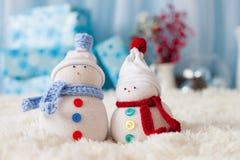 Zwei handgemachte Schneemänner mit Weihnachtshintergrund auf weißem Pelz Lizenzfreie Stockfotos
