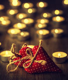 Zwei handgemachte Valentinsgrußherzen, brennende Kerzen, romantische Atmosphäre Zwei Innere auf einem hölzernen Vorstand Zwei ver Stockfotografie