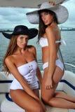 Zwei heiße Badeanzugmodelle, die auf der Luxusyacht aufwerfen Stockfoto