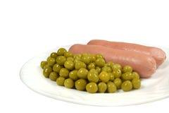 Zwei heiße gekochte Würste mit in Büchsen konservierten grünen Erbsen dienten zum Frühstück auf einer weißen Platte Lizenzfreie Stockfotos