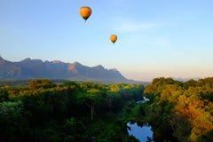 Zwei Heißluftballone, die über afrikanische Landschaft reiten Lizenzfreie Stockfotos