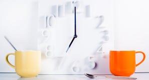 Zwei helle Becher Tee oder Kaffee zum Frühstück mit Uhr auf dem backgroung 7 morgens Lizenzfreie Stockfotografie