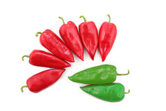 Zwei hellgrüne und sechs rote Gemüsepaprikas auf einem weißen Hintergrund Stockfotos