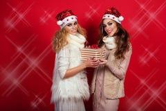 Zwei herrliche Freundinnen mit dem Glänzen lächelt tragende Sankt-Hüte und wärmt die wollenen Schals, die Präsentkarton geben Lizenzfreies Stockbild