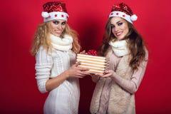 Zwei herrliche Freundinnen mit dem Glänzen lächelt tragende Sankt-Hüte und wärmt die wollenen Schals, die Präsentkarton geben Lizenzfreie Stockfotos