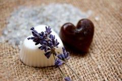 Zwei Herz-Seifen, Lavendel-Zweige und Badesalz auf Jutefaser-Unterlage Lizenzfreie Stockfotografie
