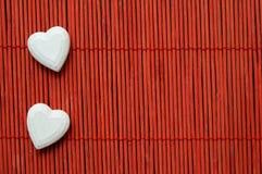 Zwei Herzen auf dem roten Bambus gezeichnet stockbilder