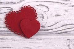 Zwei Herzen auf einem weißen hölzernen Hintergrund Stockbilder