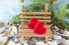 Zwei Herzen auf einer Miniaturholzbank Stockfoto