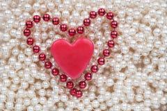 Zwei Herzen, die auf den weißen Perlen liegen Lizenzfreie Stockfotografie