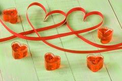 Zwei Herzen gemacht vom roten Papierband mit den Kerzen lokalisiert auf weißem Hintergrund Stockfotos