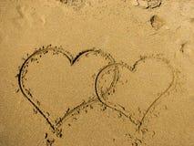 Zwei Herzen gezeichnet auf Sand eines Strandes lizenzfreie stockbilder