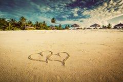 Zwei Herzen gezeichnet auf Sand eines tropischen Strandes weinlese lizenzfreie stockbilder